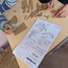 Élèves en train de construire une maquette Kit et Colle