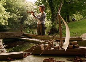 Enfant avec sa maquette d'un bateau en carton le long de la Loire