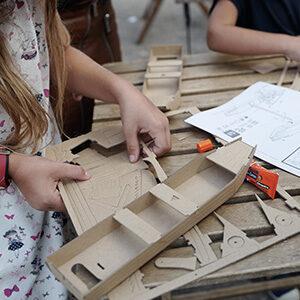 Enfant découpant les pièces pour sa maquette en carton